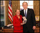 President George W. Bush stands with Kathy Downing after presenting her with the 2008 Presidential Citizens Medal Wednesday, Dec. 10, 2008, on behalf of her husband Gen. Wayne A. Downing, in the Oval Office of the White House. White House photo by Chris Greenberg
