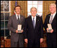 President George W. Bush stands with Jeff Miller and Earl Morse after presenting them with the 2008 Presidential Citizens Medal Wednesday, Dec. 10, 2008, in the Oval Office of the White House. White House photo by Chris Greenberg