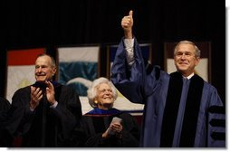 With former President George H.W. Bush and Mrs. Barbara Bush looking on, President George W. Bush gives the thumbs-up to the audience as he stands onstage Friday, Dec. 12, 2008, in Reed Arena where he delivered the commencement address at Texas A& M University in College Station, Texas. White House photo by Eric Draper