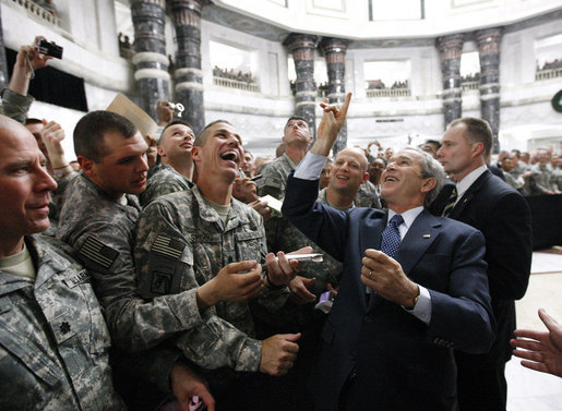"President George W. Bush gestures the ""hook'em horns"" sign of the University of Texas to U.S. military personnel in the balcony, as he meets with U.S. military and diplomatic personnel Sunday, Dec, 14, 2008, at the Al Faw Palace-Camp Victory in Baghdad. White House photo by Eric Draper"