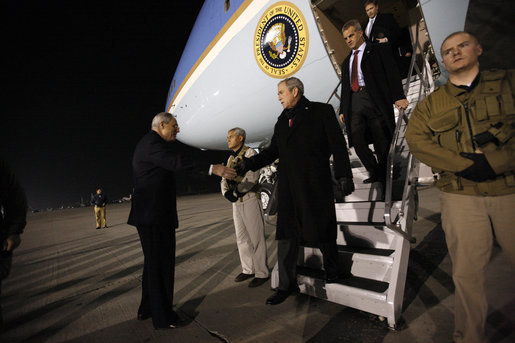 "President George W. Bush is greeted as he deplanes Air Force One Monday, Dec. 15, 2008, after arriving in the pre-dawn hours in Afghanistan. The President visited with troops at Bagram Air Base, thanking them for their service and telling them, ""I am proud to be with brave souls serving the United States of America."" White House photo by Eric Draper"