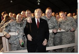 "President George W. Bush pauses for photos with troops at Bagram Air Base Monday, Dec. 15, 2008, in Afghanistan. The President made the pre-dawn visit to the base before meeting with President Hamid Karzai in Kabul. During his remarks to the troops, the President said, ""What you're doing in Afghanistan is important, it is courageous, and it is selfless. It's akin to what American troops did in places like Normandy and Iwo Jima and Korea. Your generation is every bit as great as any that has come before. And the work you do every day is shaping history for generations to come.""  White House photo by Eric Draper"