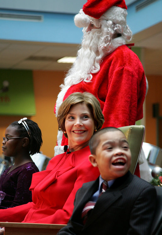 Mrs. Laura Bush watches Barney Cam VII: A Red, White & Blue Christmas as it debuts for children at Children's National Medical Center in Washington, D.C. on Dec. 15, 2008. With Mrs. Bush are her two patient escort volunteers, Dania Jecty, left, age 11, and Elmer Reyes, age 13. Visiting the hospital is an annual tradition for Mrs. Bush, and one she says she will miss. White House photo by Joyce N. Boghosian