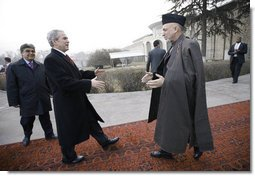 President George W. Bush is greeted by President Hamid Karzai upon arrival Monday morning, Dec. 15, 2008, at the Afghanistan leader's presidential palace in Kabul.  White House photo by Eric Draper