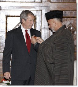 "President George W. Bush is presented the Ghazi Amir Amanullah Khan Insignia by Afghanistan's President Hamid Karzai Monday, Dec. 15, 2008, for his efforts in rebuilding the country. The presentation came during a surprise visit to Kabul about which the President said, ""I want to be in Afghanistan to say 'thank you' to President Karzai, to let the people of Afghanistan know that the United States has stood with them and will stand with them.""  White House photo by Eric Draper"