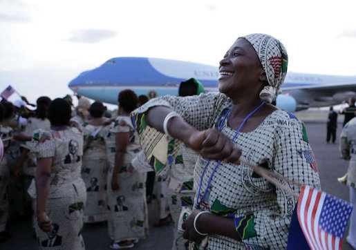 A woman waves a U.S. flag as Air Force One arrives at Julius Nyerere International Airport Saturday in Dar es Salaam. The arrival of President George W. Bush and Mrs. Laura Bush brought thousands in welcome to the streets of the country's capitol. White House photo by Chris Greenberg