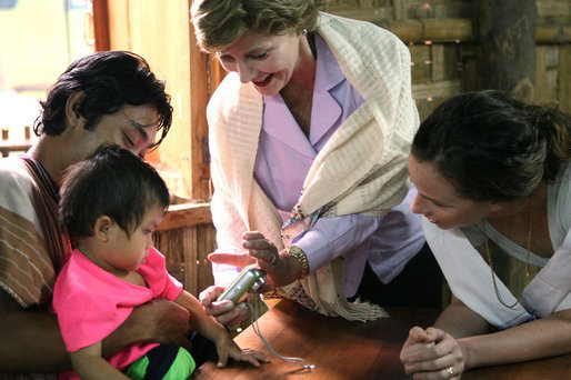 Mrs. Laura Bush and daughter Barbara Bush, show a camera to a young family at the Mae La Refugee Camp August 7, 2008, in Mae Sot, Thailand. White House photo by Shealah Craighead