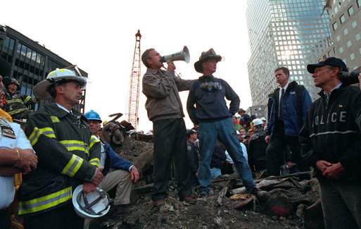 With retired firefighter Bob Beckwith standing next to him, President George W. Bush uses a bullhorn to address rescue workers Sept. 14, 2001, at Ground Zero, the site of the terrorist attack on the World Trade Center. White House photo by Eric Draper