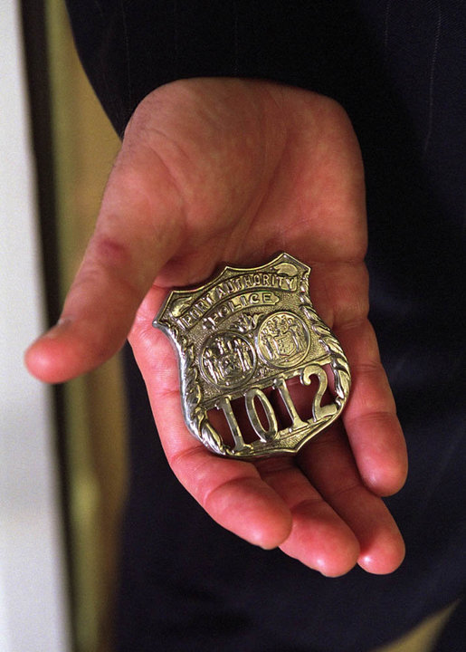 President George W. Bush holds a Port Authority Police Shield #1012 in his hand in the Oval Office, Oct. 15, 2001, at the White House. The badge was worn by George Howard when he was killed responding to the terrorist attack on the World Trade Center, and was presented to the President by Officer Howard's mother, Arlene Howard. White House photo by Eric Draper