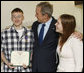 President George W. Bush congratulates U.S. Army PFC Joseph Devan of Baltimore, Md., after presenting him with a Purple Heart Monday, Dec. 22, 2008, during a visit to Walter Reed Army Medical Center, where the soldier is recovering from injuries suffered in Operation Iraqi Freedom. With them is PFC Devan's wife, Stephanie. White House photo by Eric Draper