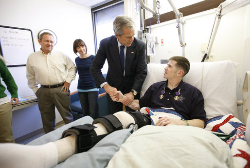 President George W. Bush shakes hands with U.S. Army Staff Sgt. Kyle Stipp of Avon, Ind., after presenting him with two Purple Hearts Monday, Dec. 22, 2008, during a visit to Walter Reed Army Medical Center where the soldier is recovering from wounds suffered in Operation Iraqi Freedom. Looking on are his wife, Megan, and father, Mitch Stipp. White House photo by Eric Draper