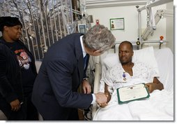President George W. Bush shakes the hand of U.S. Army Sgt. First Class Neal Boyd of Haynesville, La., after presenting him a Purple Heart during a visit Monday, Dec. 22, 2008, to Walter Reed Army Medical Center, where the soldier is recovering from injuries received in Operation Iraqi Freedom. Looking on his SFC Boyd's wife, Joyce. White House photo by Eric Draper