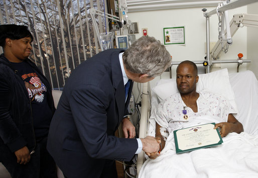 President George W. Bush shakes the hand of U.S. Army Sgt. First Class Neal Boyd of Haynesville, La., after presenting him a Purple Heart during a visit Monday, Dec. 22, 2008, to Walter Reed Army Medical Center, where the soldier is recovering from injuries received in Operation Iraqi Freedom. Looking on is SFC Boyd's wife, Joyce. White House photo by Eric Draper