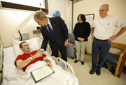 President George W. Bush shakes the hand of U.S. Army PFC Lukas Shook of Strafford, Mo., after presenting him with a Purple Heart Monday, Dec. 22, 2008, during a visit to Walter Reed Army Medical Center, where the soldier is recovering from injuries received in Operation Iraqi Freedom. Looking on are PFC Shook's mother and father, Dennis and Cynthia Shook. White House photo by Eric Draper