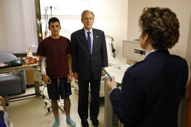 President George W. Bush stands with U.S. Army Specialist Fernando Aguilar of Tucson, Ariz., Monday, Dec. 22, 2008 at Walter Reed Army Medical Center in Washington, D.C., as a White House military aide reads Aguilar's Purple Heart citation. Aguilar is recovering from injuries sustained when two hand grenades were thrown at his vehicle while on patrol in support of Operation Iraqi Freedom. White House photo by Eric Draper