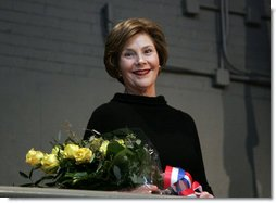 Mrs. Laura Bush stands with a bouquet presented along with the Department of Defense Outstanding Public Service Award by U.S. Secretary of Defense Robert Gates during a military appreciation Tuesday, Jan. 6, 2009, in honor of President George W. Bush's tenure as Commander-in-Chief.  White House photo by Joyce N. Boghosian
