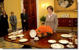 Mrs. Laura Bush meets reporters as she announces two new White House china patterns, Wednesday, Jan. 7, 2009 in the Family Dining Room of the State Floor of the White House for their unveiling of the George W. Bush State China and the Magnolia Residence China. The George W. Bush State China was inspired from a Madison-era dinner service. The Magnolia Residence China is in the picture foreground and the George W. Bush State China is on the left side of the table. With Mrs. Bush from left are Amy Zantsinger, White House Social Secretary, Nancy Clarke, White House Florist, and Bill Allman, White House Curator. White House photo by Shealah Craighead