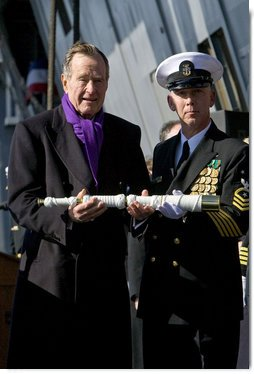 Former President George H.W. Bush presents a long glass to the First Officer of the Deck to set the first watch Saturday, Jan. 10, 2009, during commissioning ceremonies for the USS George H.W. Bush (CVN 77) aircraft carrier in Norfolk, Va. White House photo by David Bohrer
