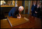 Vice President Dick Cheney signs the inside of the top drawer of his desk in the Vice President's Ceremonial Office Monday, Jan. 12, 2009, at the Eisenhower Executive Office Building in Washington, D.C. The desk, constructed in 1902 and first used by President Theodore Roosevelt, has been signed by various presidents and vice presidents since the 1940s. Mrs. Lynne Cheney is seen at right. White House photo by David Bohrer