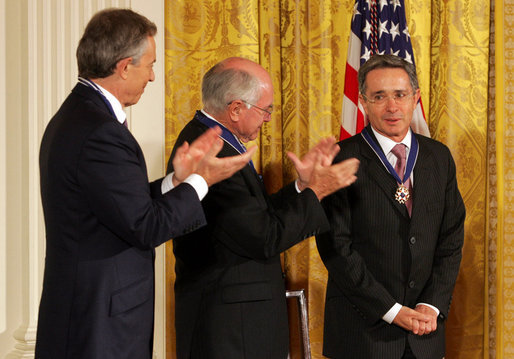 Colombian President Alvaro Uribe is congratulated by former Prime Minister John Howard of Australia, and former Prime Minister Tony Blair, left, of the United Kingdom after he was honored by President George W. Bush with the 2009 Presidential Medal of Freedom during ceremonies honoring all three leaders with America's highest civil award. White House photo by Joyce N. Boghosian