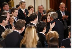 President George W. Bush embraces his daughters Barbara and Jenna as he receives a standing ovation from invited guests and members of his staff and Cabinet at the conclusion of his televised farewell address to the nation Thursday evening, Jan. 15. 2009, in the East Room of the White House. White House photo by Chris Greenberg