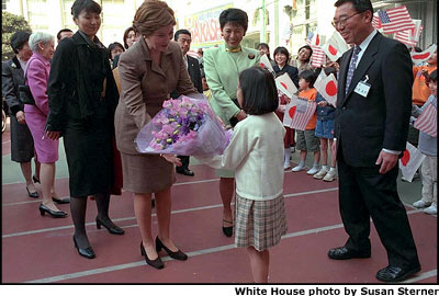 President Goerge W. Bush greets children during a visit to Korea's Blue House with South Korean President Kim Dae-Jung Feb. 20, 2002.