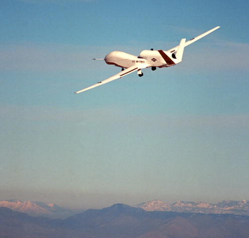 A white Global Hawk unmanned aircraft on a test flight over Edwards Air Force Base, California.  Mountains are in the background.