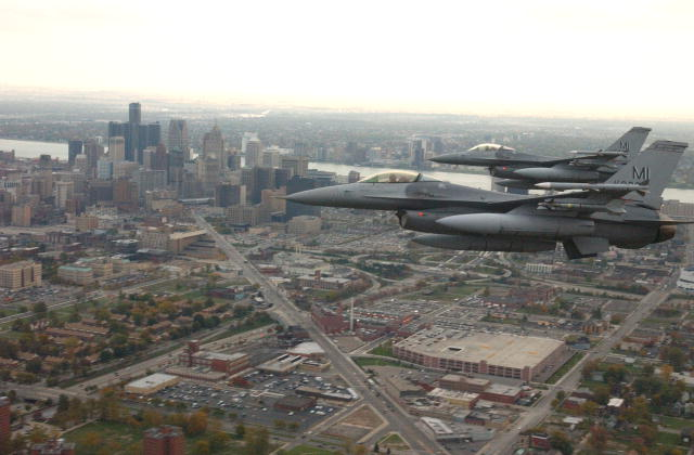 Two F-16s fly over Detroit.  Skyscrapers and the Detroit River are in the background.