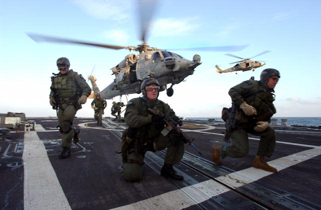 U.S. Navy Seals fastrope onto the fantail of USS Oscar-Austin during a Joint Task Force Exercise.