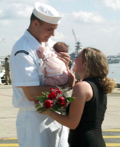 A sailor is greeted with flowers by his wife and infant upon his return from a tour aboard USS Ticonderoga.