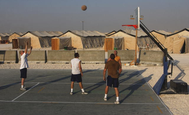 Four male service members play basketball in the desert of Al Udeid Air Base, Qatar.  Tent-like housing structures are in the background.