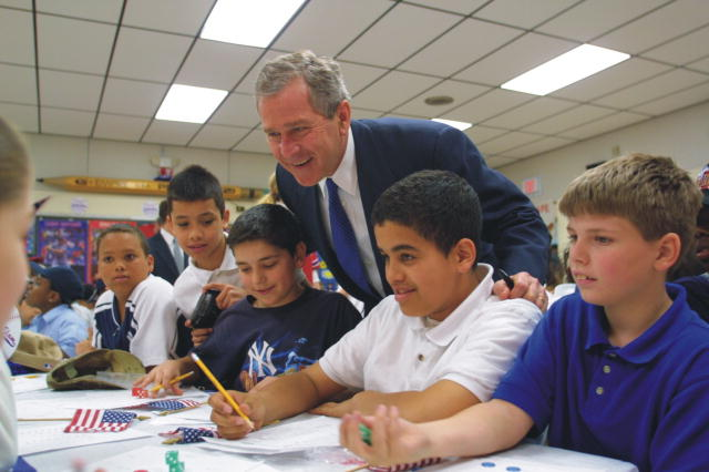 President Bush is leaning over elementary school students who are sitting and working at a table.