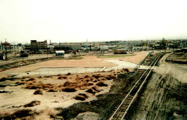 The photo shows an expanse of empty lots, scrubby plants, unused railroad tracks and run down buildings.