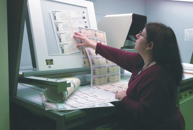 A worker carefully checks the quality of recently printed savings bonds.