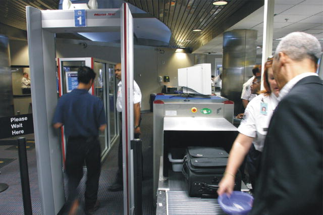 The picture shows passengers being screened at an airport checkpoint.