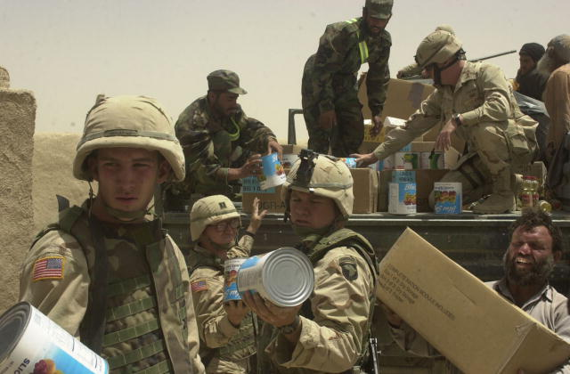 U.S. and Afghan soldiers unload a truck full of food and supplies in Afghanistan.