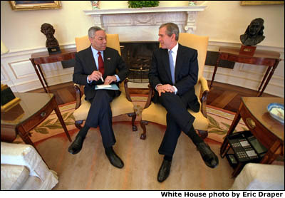 President Bush and Secretary Colin Powell sit in yellow chairs in front of the Oval Office fireplace. White House photo by Eric Draper.