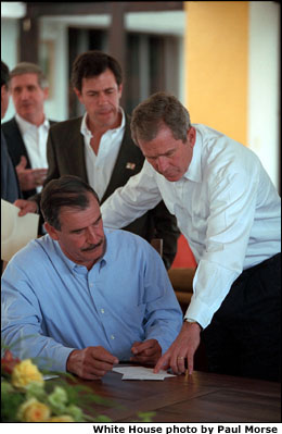Mexican President Vicente Fox is seated. President Bush is standing next to him. White House photo by Paul Morse.