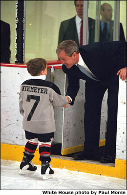 President Bush shakes hands with a young boy dressed in a hockey uniform. White House photo by Paul Morse.