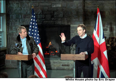 President Bush and Prime Minister Tony Blair stand in front of the U.S. and British flags. White House photo by Eric Draper.