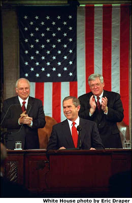 President Bush speaks to Congress. Vice President Cheney and Speaker Hastert stand behind him and applaud. White House photo by Eric Draper.