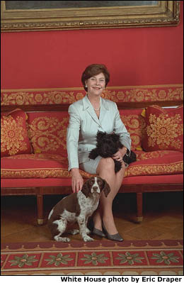 Laura Bush is seated on a red sofa with dogs Barney and Spotty. White House photo by Eric Draper.