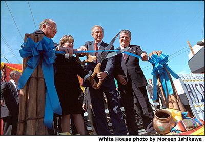 With help from officials from Albuquerque's Hispanic Chamber of Commerce, President Bush cuts the ribbon to open the Barelas Job Opportunity Center Aug 15. White House photo by Moreen Ishikawa.