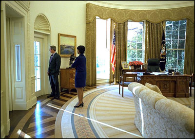 President George W. Bush talks alone with Dr. Condoleezza Rice in the Oval Office Nov. 27, 2002.