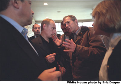 President George W. Bush and Russian President Vladimir Putin meet as Russian and White House staff listen moments before the departure of President and Mrs. Putin from the Bush Ranch, Thursday, Nov. 15, 2001. White House photo by Eric Draper.