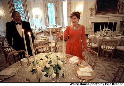 With just minutes to go before hosting her first State Dinner, Laura Bush lights the first candles of the evening with a little help from maitre d' George Hannie. White House photo by Eric Draper.
