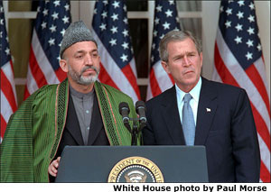 President George W. Bush listens to Chairman of the Afghan Interim Authority Hamid Karzai during their joint press conference in the Rose Garden, January 28. White House photo by Paul Morse.