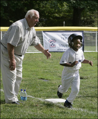 Hall of Fame baseball manager Tommy Lasorda urges on a player from the Wrigley Little League Dodgers of Los Angeles, as he runs for home against the Inner City Little League of Brooklyn, N.Y., Sunday, July 15, 2007, during the White House Tee Ball Game celebrating the legacy of Jackie Robinson on the South Lawn of the White House. Brooklyn and Los Angeles represent the two home cities of Robinson's team.